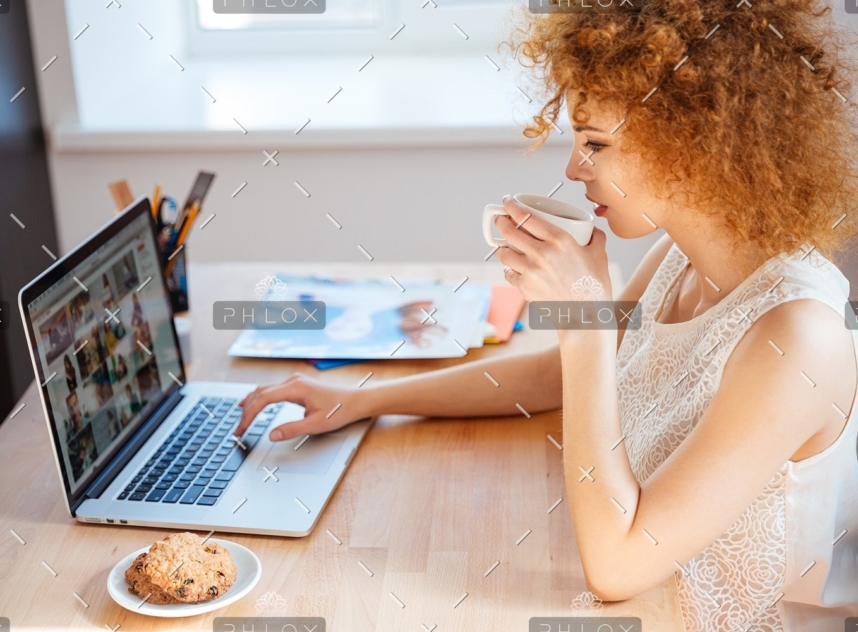 demo-attachment-493-woman-photographer-drinking-coffee-and-working-PJNBP6U